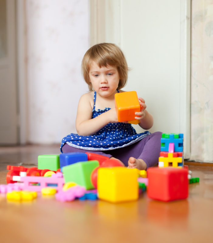 3 years girl plays with toys in school